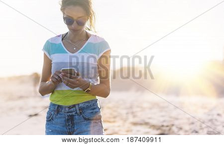 Hipster girl photograph on smart phone gadget in sand coastline beach mock up of blank screen. Traveler hold and using in female hand mobile on background seascape horizon. Tourist look on blue sun ocean