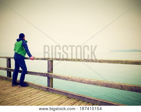 Alone Man At Handrail, Autumn Misty Morning On Sea Pier. Depressive
