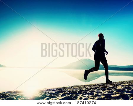 Healthy Lifestyle. Tall Young Man Runner Is Running On Sunrise Seaside. Man Jump In Sand