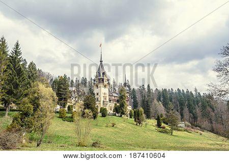 SINAIA, ROMANIA - APRIL 4, 2017: The Peles Castle from Sinaia Romania gardens with green grass and trees.