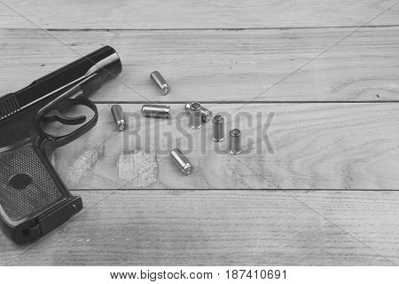 Traumatic pistol with bullets and cartridge on the wooden surface, black and white effect