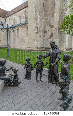 ALBA IULIA ROMANIA - APRIL 29 2017: Group of bronze statues in Alba Carolina Citadel square depicting Saint Anthony - the patron saint of finding things or lost people - surrounded by children.