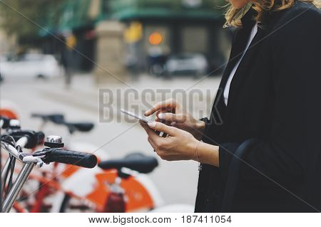 Young businesswomen in black suit and umbrella using smartphone biking and going to work by city bicycle on urban street hipster girl holding mobile gadget ecology environment concept poster