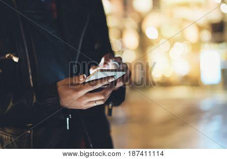 Girl pointing finger on screen smartphone on background illumination glow bokeh light in night atmospheric christmas city hipster using in female hands mobile phone; mockup glitter street