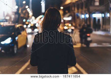 Hipster girl in black leather jacket from back on background illumination glow bokeh light in night atmospheric christmas city hipster costs at a stop in headlights auto taxi; mockup glitter