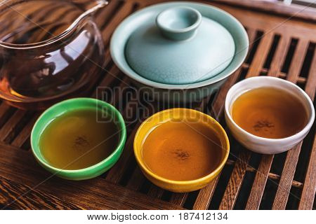 Asian tea set on wooden tea board, Colorful pialas or tea bowls, gaiwan, Chinese tea ceremony