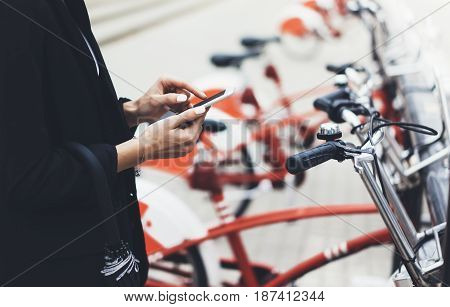 Young businesswomen in black suit and umbrella using smartphone biking and going to work by city bicycle on urban street hipster girl holding mobile gadget ecology environment concept