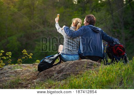 Young couple hikers resting and enjoying beautiful nature view at sunset. A woman is taking photo. Travel vacation holidays and adventure concept. Forest Mountain landscape background