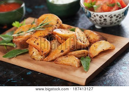 Spicy roasted potato wedges with herbs on wooden board