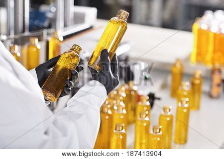 Manufacturing Concept. Factory Worker Holding Two Glass Bottles With Yellow Liquid Comparing Quality