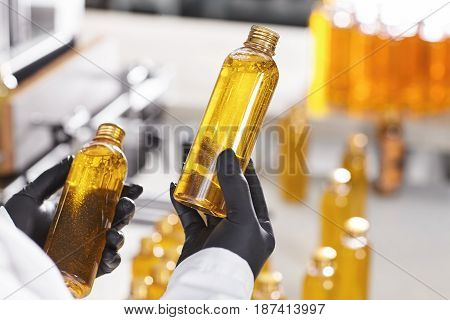 Lean Production Of Cosmetics On Factory. Close-up Portrait Of Hands In Black Rubber Gloves Holding T