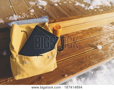 Yellow backpack thermos with hot drink and hipster gadget tablet with a clean blank screen on a background of winter snow landscape. Technology mockup on wooden pier templates in travel nature