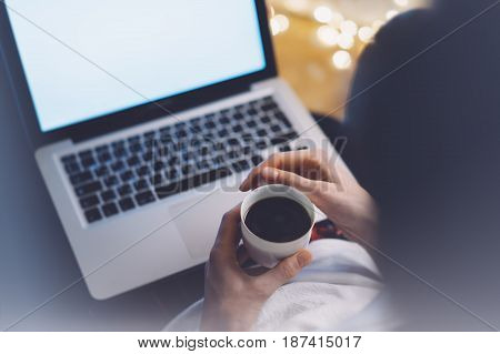 Girl in a chair in a homely atmosphere with an open laptop with a empty blank screen monitor and a cup of coffee or tea on the background bokeh light freelancer hipster working at home in a homely atmosphere using digital computer with blank template copy