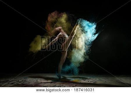Female sexy gymnast in gray bodysuit shot in a jump on black background in a cloud of blue and yellow dust all over body