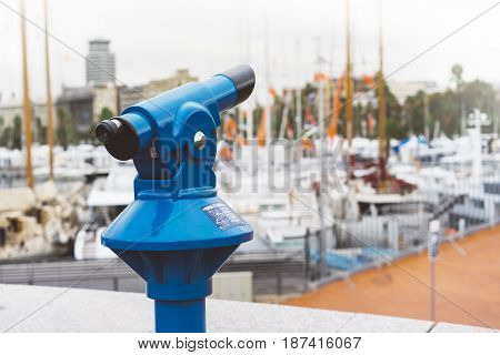 Touristic telescope look at the city with view of Barcelona Spain close up old blue binoculars on background viewpoint the pier port yacht coin operated in panorama observation nature mockup