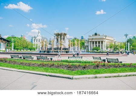 Moscow, Russia - May 18, 2017: people walking near famous fountain Friendship of Nations in the park of VDNKh - Exhibition of Achievements of National Economy