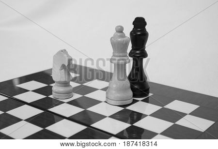 The chess pieces are placed on the chessboard. Checkmate. Chess. Black and white.