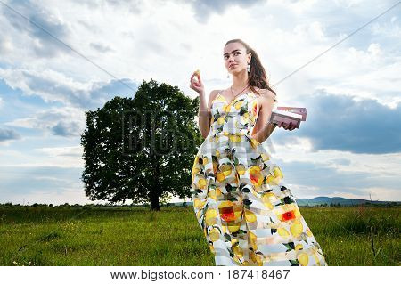 Beautiful Young Free Girl In A Light Dress With Macaroons, In The Middle Of A Spacious Field With A