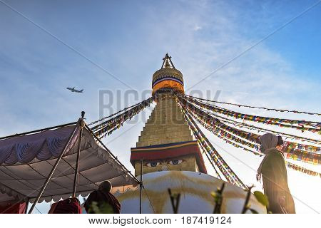 Dawn on a Buddhist stupa of Boudha. Sunshine the woman in a medical mask makes kora around a stupa a tent and the taking-off passenger plane.