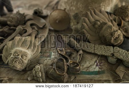 Scissors and parts of preparations for creation of bronze statues of Buddhist deities and bodhisattvas in traditional Tibetan style lying on a table in a workshop.
