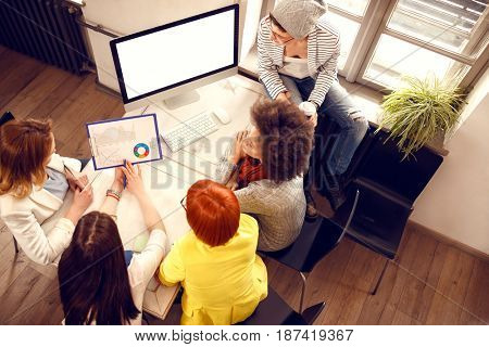 Young women at creative work with chart and computer in office