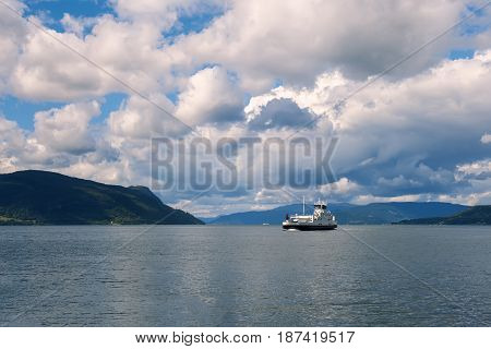 The ferry sails along the Norwegian fjord in Sunny day with beautiful clouds and mountains in background.