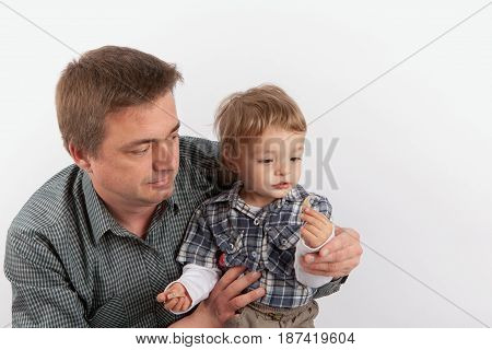 Hearing aids in the Family - Father showing his hearing aids to his small son. The man's hearing aids in the toddler boy hands.
