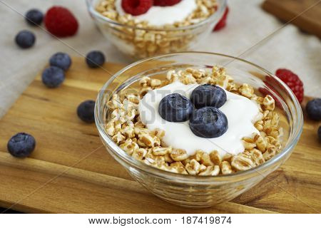Healthy diet breakfast with a bowl of yogurt spelt flakes and mixed fresh berries fruit.