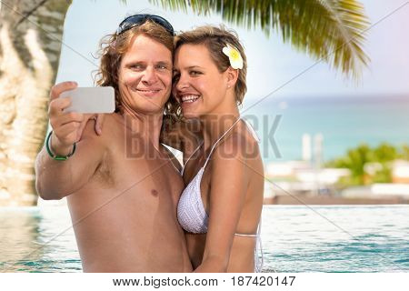 Couple taking selfie on smartphone in swimming pool