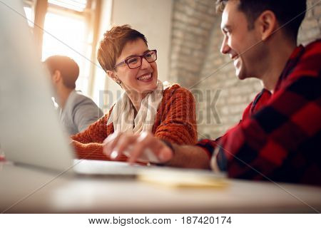 smiling designers in good mood working together in office