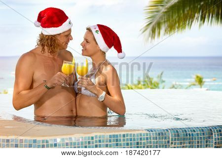 Love couple on tropical,  Christmas holiday, toasted with cocktails and looking at each other