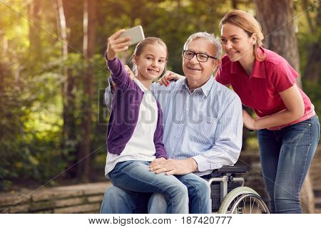 daughter with her disabled father in wheelchair and granddaughter using phone for selfie in the park