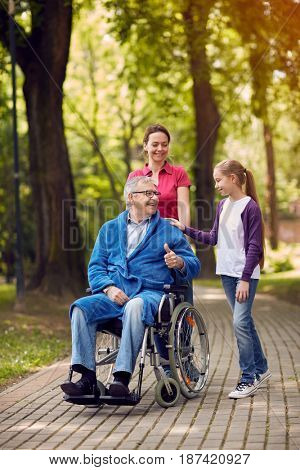 cheerful daughter and grandchildren visiting senior disabled father in park