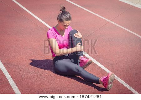 Female sitting on running track and holding her injured leg. Accident during jogging