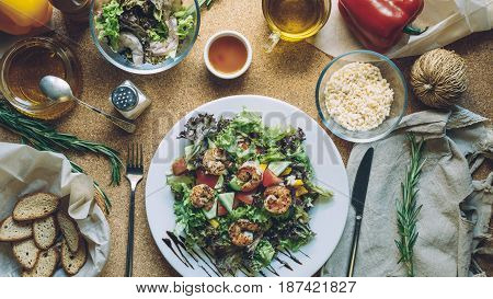 Concept making tasty and healthy food at home. Ingredients and cutlery around fresh salad with shrimps. Serving option. Flat lay style
