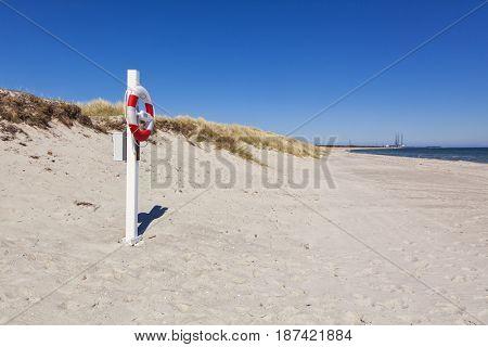 Lifebelt at the beach of Grenaa, Djursland peninsula, Jutland, Denmark. Harbor in background.
