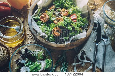 Fresh and healthy salad with shrimps, ingredients on wooden surface tasty and healthy food concept