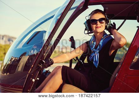 Attractive woman pilot sitting in the helicopter
