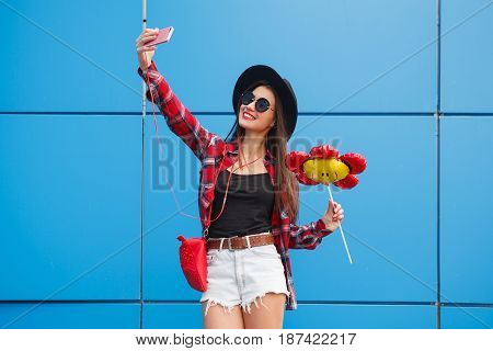 Fashion portrait of pretty smiling and woman in sunglasses with smartphone against the colorful blue wall. Make selfie with balloon in her hand. Outdoor