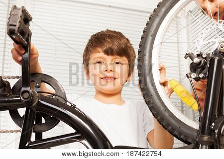 Close-up portrait of smiling six years old boy repairing his bicycle indoors