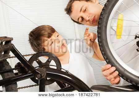 Portrait of kid boy checking the wheels of the bicycle together with his father at the garage