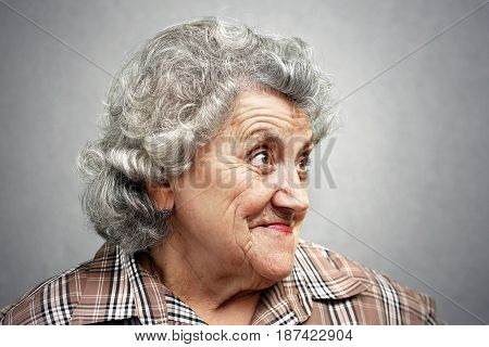 Emotional elderly woman face on a grey background