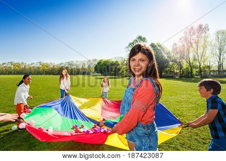 Portrait of young girl standing in a circle with her friends and holding rainbow parachute full of colorful balls