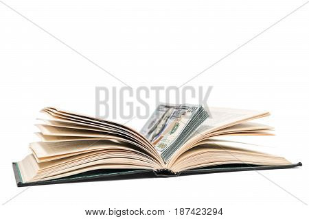 Open book with a stack of dollars lying in it, isolated on a white background