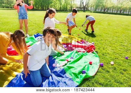 Portrait of Caucasian boy sitting in the center of playground rainbow parachute playing with his friends