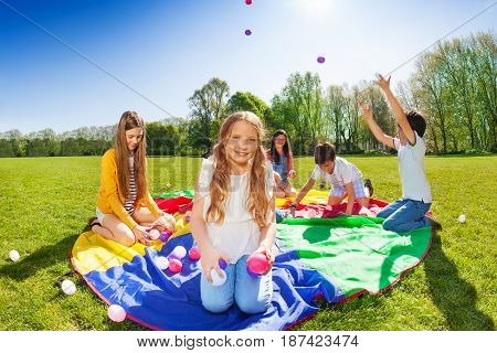 Portrait of beautiful fair-haired girl, sitting on the parachute and holding colorful balls during the game with friends outdoors