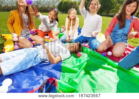 Group of diversity looking kids, playing with colorful balls, sitting or laying on rainbow parachute in the park