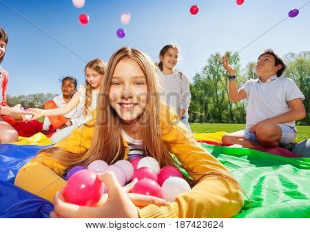 Close-up portrait of pretty blond girl laying on mat with an armful of colorful balls outdoors in the spring