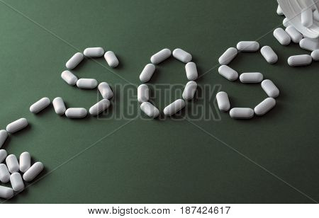 White pills on green background, which forming the word - SOS, with a blister of pills on background. Pharmaceutical or addiction narcotic or depressive or painkiller concept.