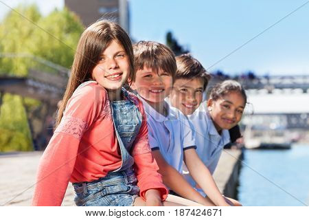 Close-up portrait of happy schoolchildren sitting in a line on bank of river in summertime